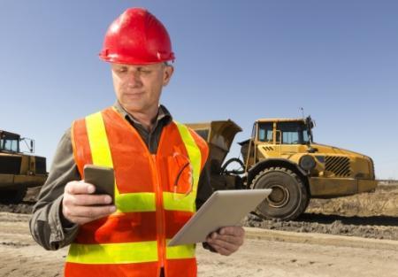 pracownik wkamizelce trzymający telefon